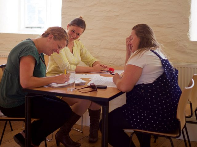 Small group of women working collectively on business support during an Unlocking Potential Breakthrough 2 Day workshop at Trelissick Gardens in Cornwall