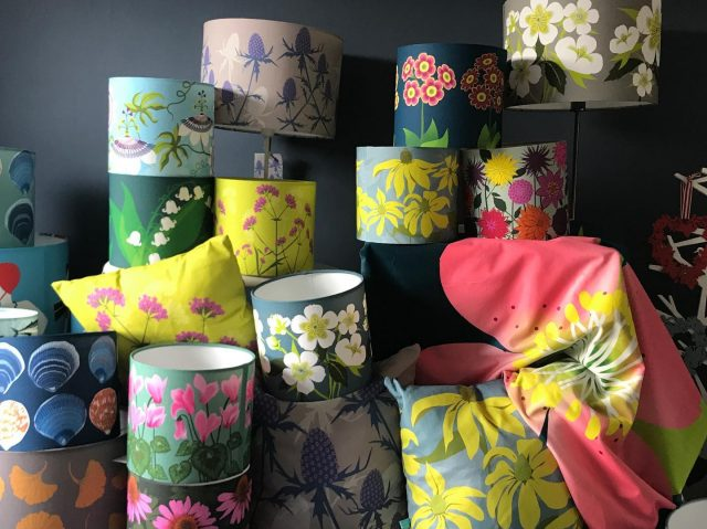 A variety of colourful lampshades and cushions