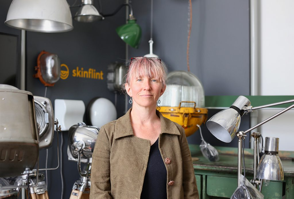 Woman indoors surrounded by metal lampshades