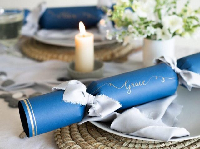 Personalised blue Christmas cracker on decorated table