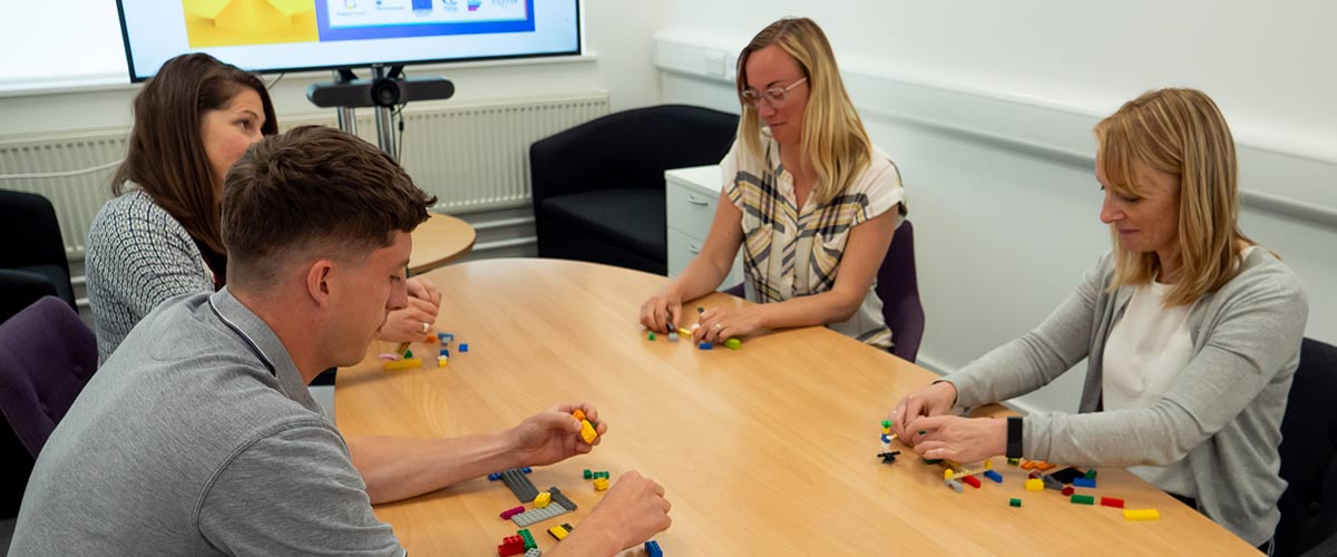 Three women and one man sat round a table playing with lego as part of a workshop type activity