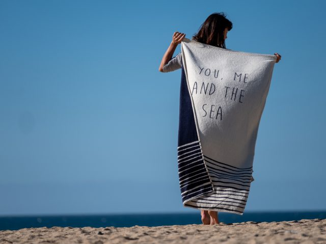Woman holding you me and the see atlantic blanket design