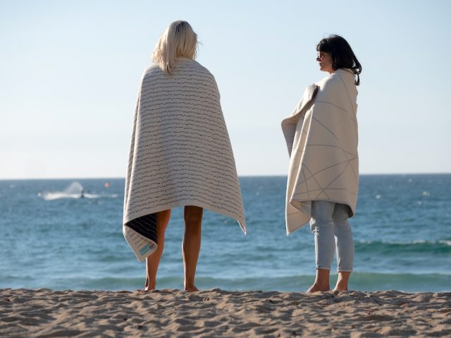 Two women on the beach wrapped in Atlantic Blankets